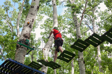 young man passes obstacles in adventure park in forest