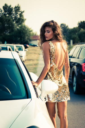 summer fashion girl in golden dress stand by the car on the road photo