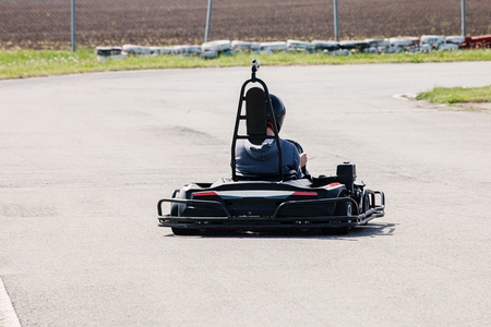 man drive go kart on track back view outdoor shot Stock Photo