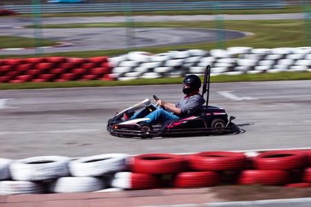 man drive go kart on track side shot