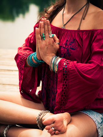 closeup young woman in a meditative yoga position wearing red tunic sit on wooden pontoon on the lake wearing lot of bracelets and rings