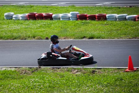 young man drive go kart on track side view outdoor shot