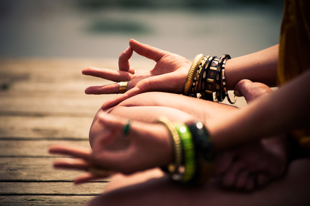 woman in a meditative yoga position sit on wooden pontoon on the lake wearing lot of bracelets and rings lower body 스톡 콘텐츠
