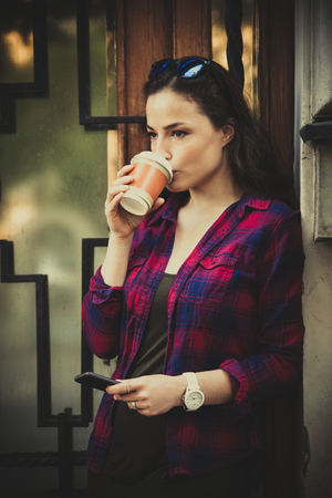 urban girl in city with smartphone and takeaway coffee in front of building entrance  summer day photo