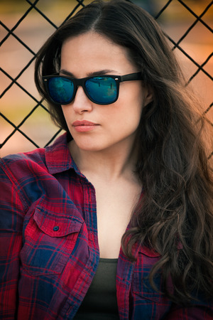 urban girl portrait with sunglasses in the city in front wire fence day shot summer photo