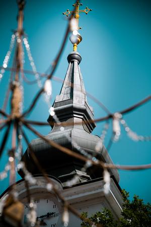 Church clock tower shot through decorative  street chandelier