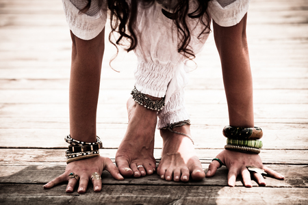 closeup of barefoot woman feet and hands practice yoga outdoor wearing white clothes and lot of bracelets, anklets and toe ring