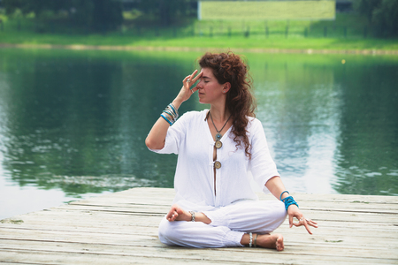young woman practice yoga breathing techniques  outdoor by the lake healthy lifestyle concept