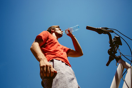 young man on a bicycle from below shot drink water hot summer day real people concept