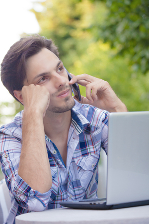 young man outdoor at terrace with laptop and  smartphone listen someone boring working online  business concept