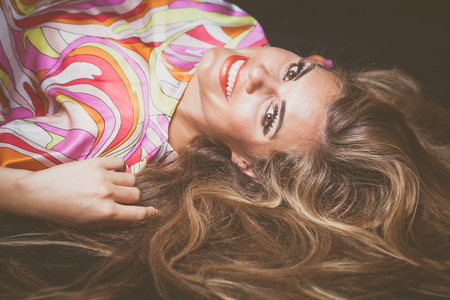 smiling young blonde beauty woman  portrait with long hair lie down studio shot Stock Photo