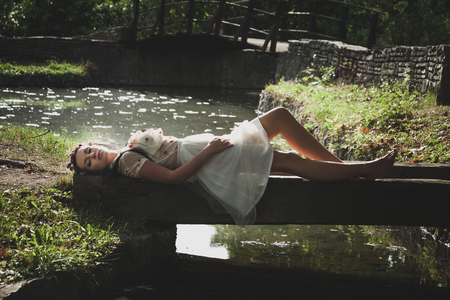 romantic style young woman lie on small wooden bridge over pond in tulle skirt and shirt with wreath of flowers in hair summer day
