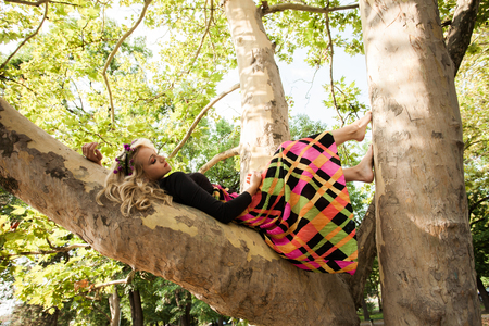 boho romantic style barefoot young blonde woman in long colorful dress lie on tree in park summer day