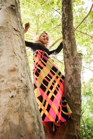 boho romantic style barefoot young blonde woman in long colorful dress stand  on tree in park summer day