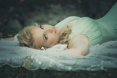 beautiful bridal portrait lie in grass with veil around her look at camera