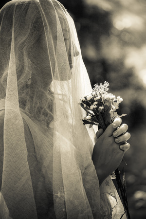 portrait of bride with veil and bouquet of wild flowers outdoor shot  summer day outdoor sepia tones