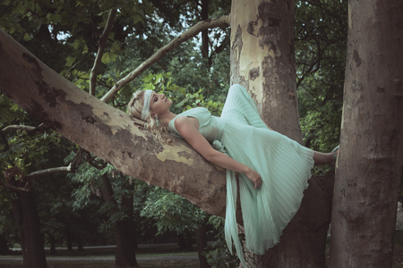 pretty young blonde woman in romantic dress lie  on tree in wood or park summer day