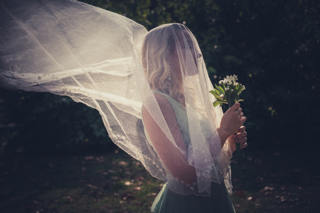 portrait of bride with veil and bouquet of wild flowers outdoor shot  summer day outdoor