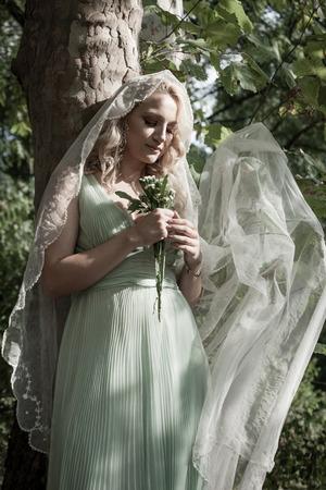 portrait of bride with veil and bouquet of wild flowers outdoor lean on tree summer day Lizenzfreie Bilder