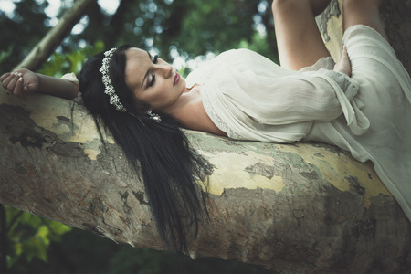 pretty young  woman in romantic dress and hair decoration  lie  on tree in wood or park summer day