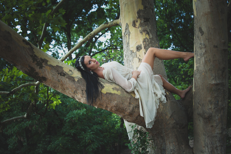 pretty young dark hair woman in romantic dress barefoot lie  on tree in wood or park summer day