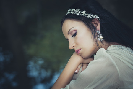 portrait of young romantic style woman with hair decoration sit by lake