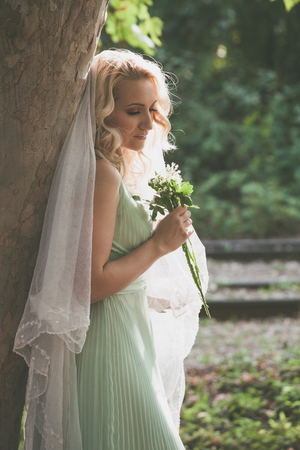 portrait of bride with veil and bouquet of wild flowers outdoor shot stand by tree  summer day