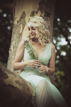 pretty young blonde woman with flowers in hand in romantic dress sit on tree in wood or park summer day Lizenzfreie Bilder