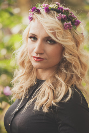 pretty young blonde woman with wreath of flowers in hair romantic style  portrait outdoor shot in park summer day