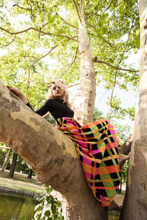 boho romantic style barefoot young blonde woman in long colorful dress sit on tree in park summer day Lizenzfreie Bilder