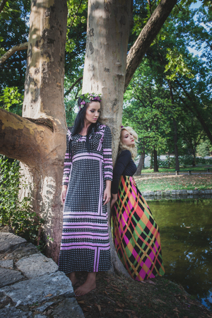 couple of boho style women in long dresses and wreath of flowers in hair by the pond in park summer day Lizenzfreie Bilder