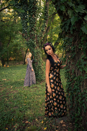 couple of boho style women in long dresses and wreath of flowers in hair in the wood