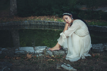 young barefoot woman in romantic dress and hair decoration sit by pond summer day
