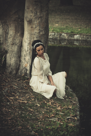 young woman in romantic dress and hair decoration sit by lake lean on tree summer day Lizenzfreie Bilder