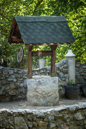 stone well with metal water bucket in traditional  mountain village