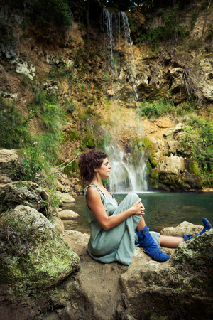 young woman practice yoga outdoor on the rocks by the waterfall summer day Lizenzfreie Bilder