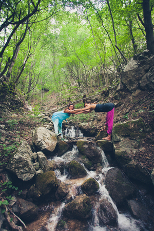couple of women enjoy in nature standing on rocks on small mountain river summer day