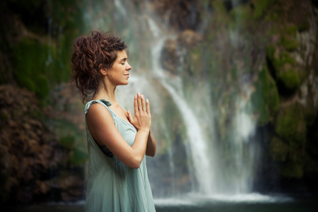 young woman practice yoga outdoor  by the waterfall summer day profile closeup