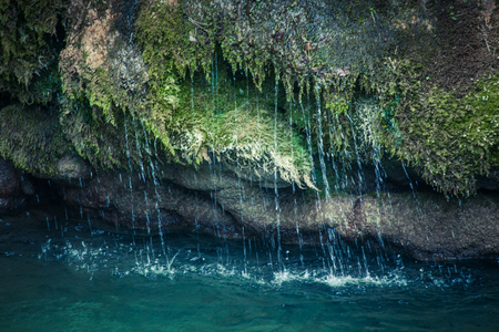 closeup of water running over moss and stones from waterfall in to lake