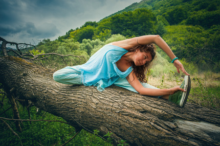 young woman practice yoga outdoor on huge fell tree on the mountain trip summer day