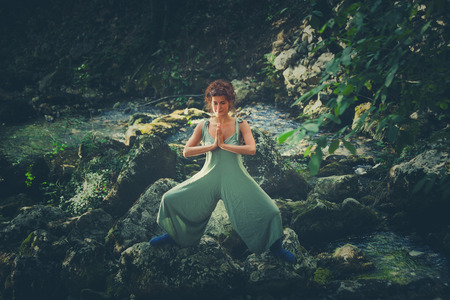 young woman practice yoga outdoor in riverbed of small mountain river summer day Lizenzfreie Bilder