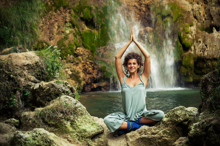 smiling young woman practice yoga outdoor on the rocks by the waterfall summer day Lizenzfreie Bilder
