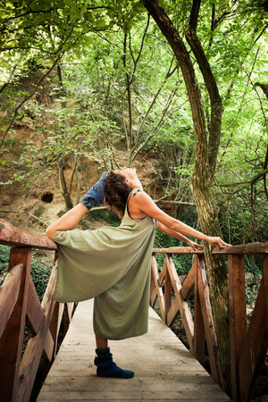 young woman practice yoga outdoor on the small wooden river bridge in the mountain summer day Lizenzfreie Bilder