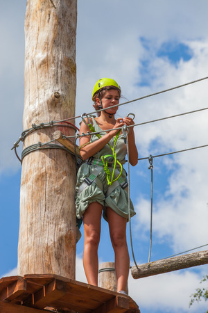 young woman in adventure park prepare for barrier use safety equipment