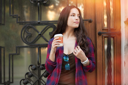 young woman with  coffee to go outdoor portrait in the city