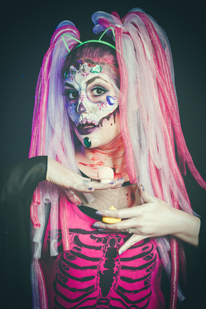 scary halloween woman with sugar skull makeup offering candy mushrooms studio shot stock photo 88183512