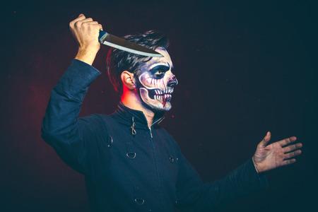 scary halloween skeleton man in jacket with big knife studio shot closeup