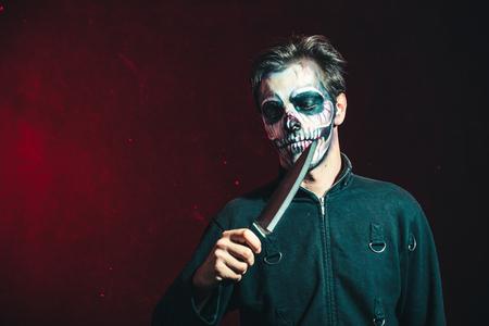 scary halloween skeleton man in jacket hold big knife studio shot closeup