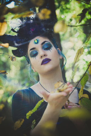 fantasy  fairy with horns in forest among  trees and branches
