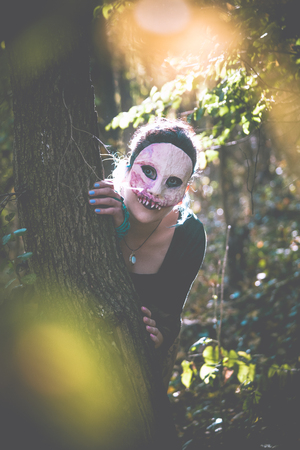 unnatural scary creature lurk behind tree in the forest